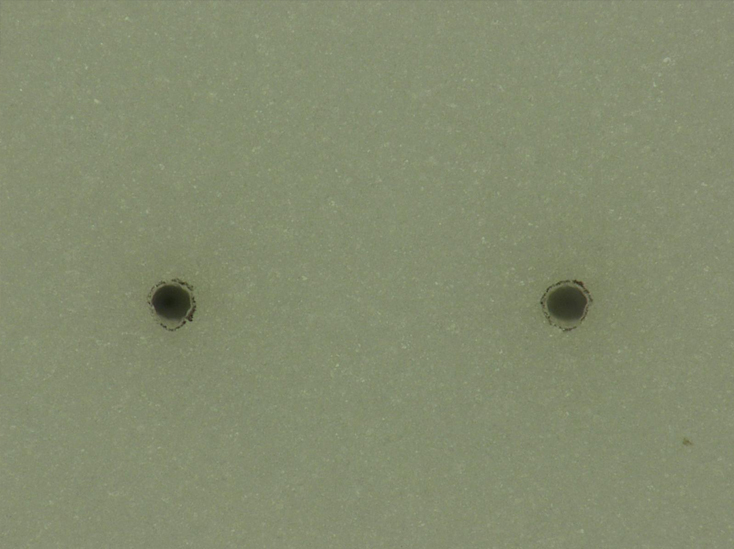Figure 4: The top side of a typical 75µm diameter via. HAZ extends 11µm out from the edge of hole and they are round to within 2.5µm. It should be noted that these vias are machined (trepanned) features, not single shots.